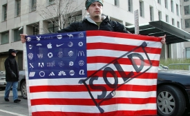A protester holds Adbuster's American Corporate flag