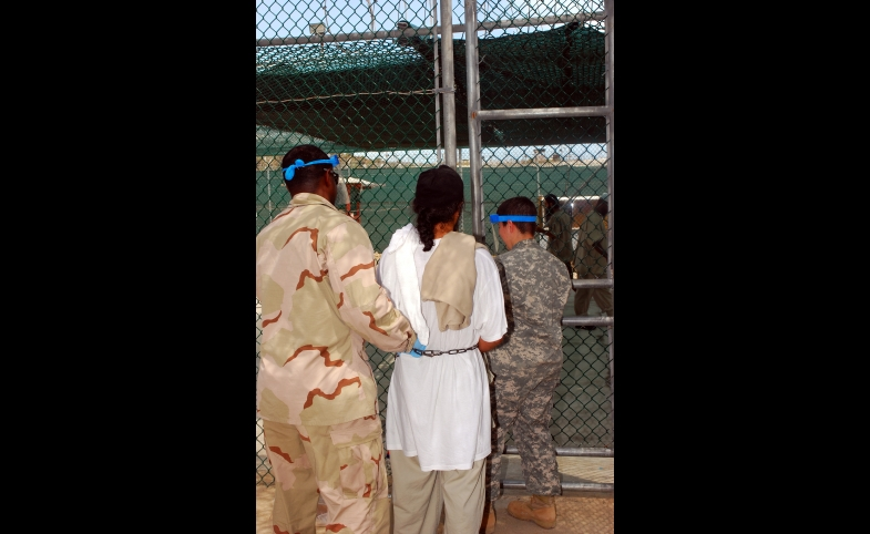 Guards escort a Guantanamo captive in chains to a recreational area