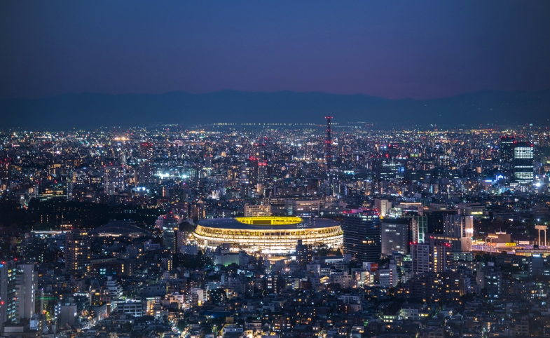 Overhead aerial view of the new National Stadium with Tokyo's skyline in twilight time, fully completed main stadium for Tokyo Olympic Summer Games 2020. Image via iStock.