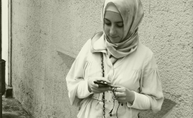 A young woman checks her smart phone