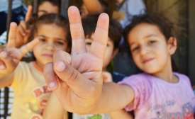 Syrian refugee children at a half-built apartment block near Reyfoun in Lebanon, close to the border with Syria, give the peace sign. The families fled Syria due to the war and are now living on a building site. (Photo: Eoghan Rice)