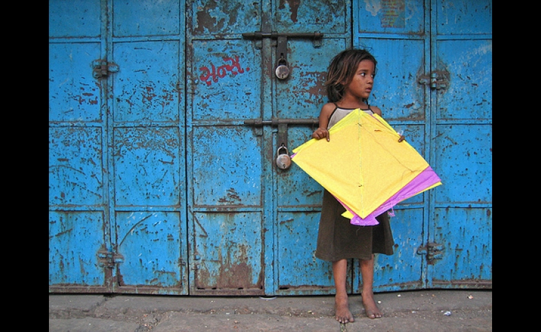 Yellow Patang. A girl from the nearby slum collecting fallen kites (patang) at Manek Chowk in the Old City.