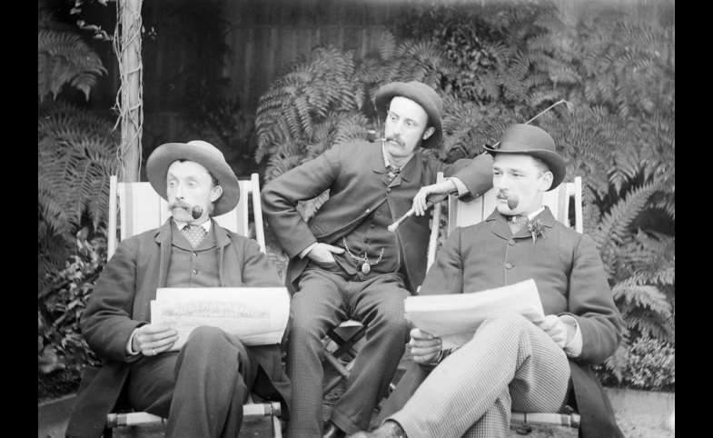 Three men sitting in deckchairs, smoking pipes and reading papers.