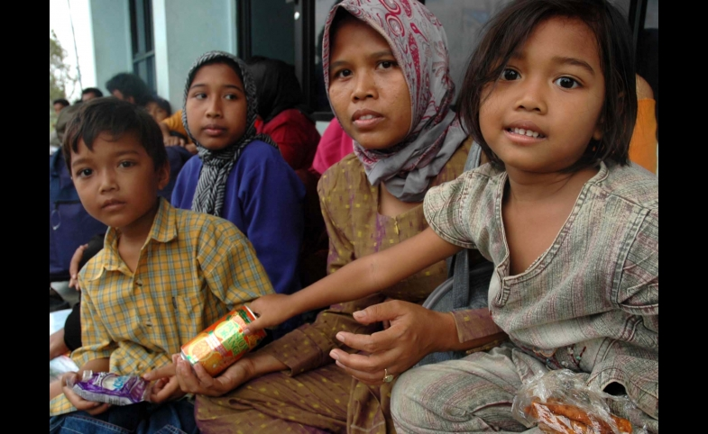 An Indonesia family waits for food from the U.S. Navy and IOM.