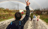 Hassan Saad, 13, who fled Idlib in Syria, flashes a victory sign while walking outside the refugees camp near the Turkish-Syrian border in the southeastern city of Yayladagi