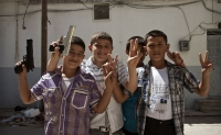 A group of young Syrian boys with toy guns mug for the camera.